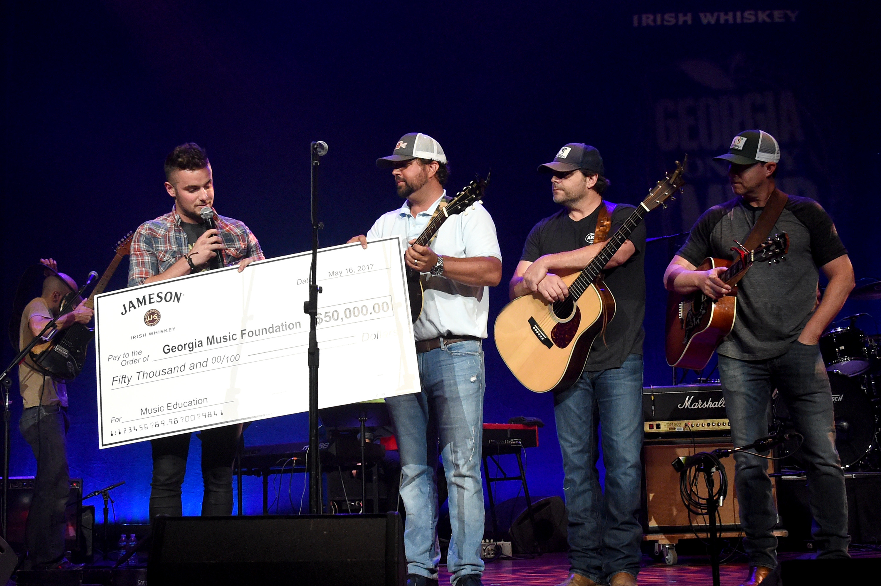 Jameson Brand Ambassador Gary Feeney presents Dallas Davidson, Rhett Akins, and Ben Hayslip with a check onstage during the 4th Annual Georgia On My Mind; Photo by Rick Diamond/Getty Images for Georgia Music Foundation