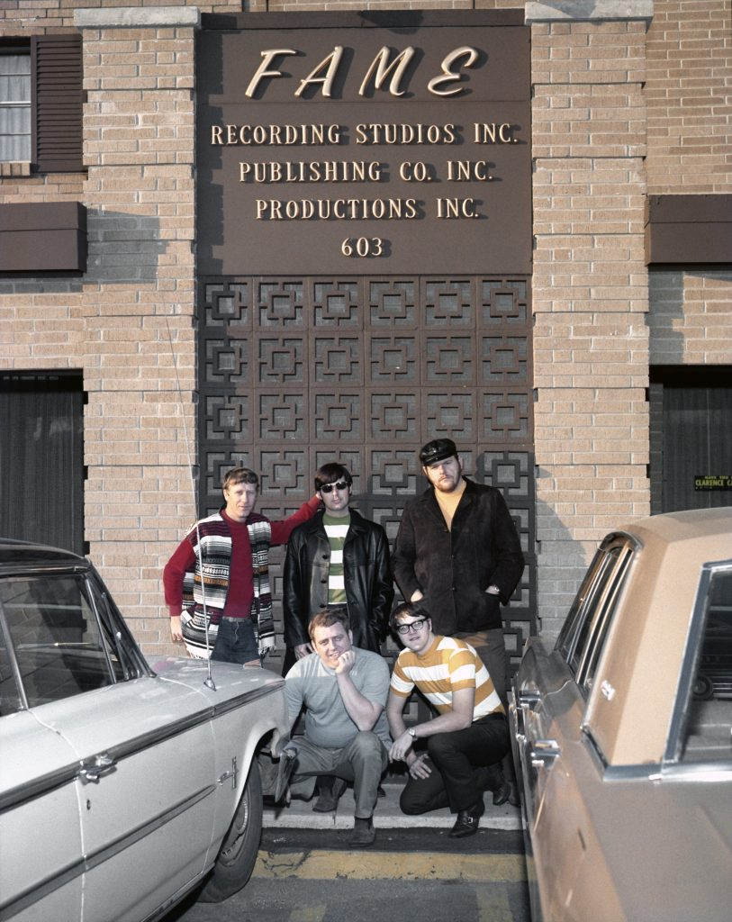 MUSCLE SHOALS, AL - 1968: Session musicians The Muscle Shoals Rhythm Section also known as the Swampers (Back L-R Junior Lowe, David Hood and Barry Beckett, Front L-R Jimmy Johnson and Roger Hawkins) pose for a portrait outside FAME Studios in 1968 in Muscle Shoals, Alabama. (Photo by House Of Fame LLC/Michael Ochs Archives/Getty Images)