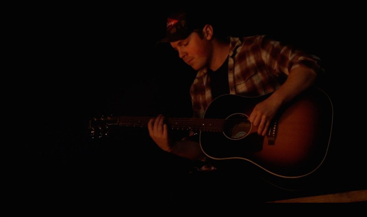 Travis Denning Stays Safe in Love With 'Sittin By a Fire' Video